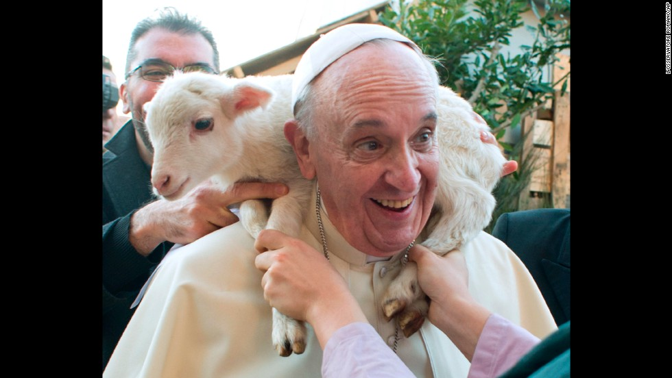 A lamb is placed around Francis' neck in January 2014 as he visits a living nativity scene staged at a church on the outskirts of Rome.